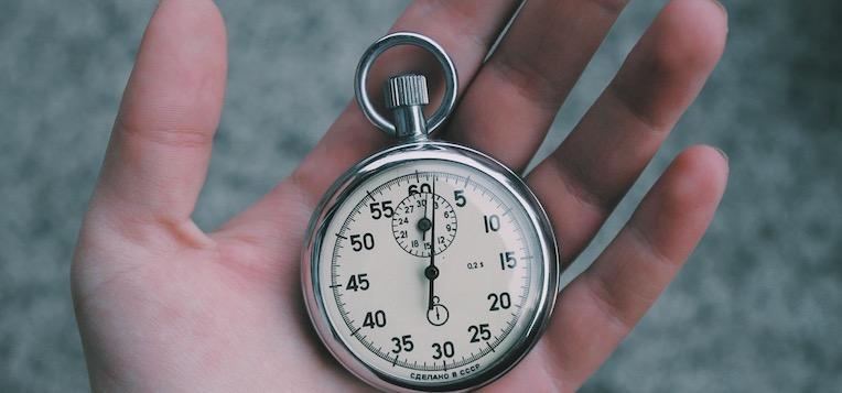 Wie oft Bizeps und Trizeps trainieren: Foto von einer Stoppuhr in einer Hand.