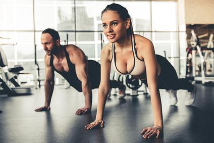Foto von einem Mann und einer Frau bei der Brust-Übung breite Liegestütze.