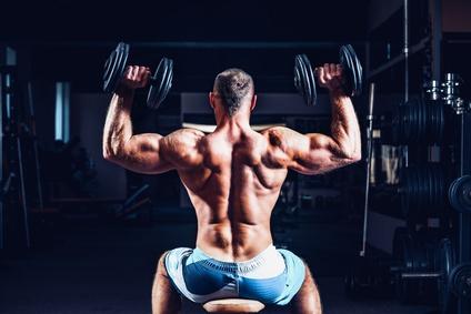 Die besten Schulterübungen: Foto vom Schulterdrücken mit Kurzhanteln.