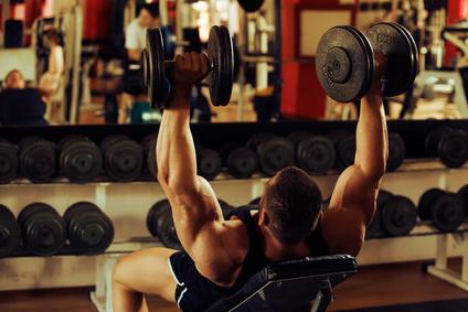 Die besten Schulter Übungen: Foto vom Schulterdrücken auf der Schrägbank mit Kurzhanteln.