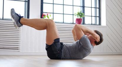 Oberkörpertraining ohne Geräte: Foto von einem Mann bei der Bauch-Übung Crunches beziehungsweise Bauchpresse.