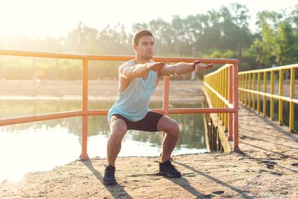 Oberkörpertraining ohne Geräte: Foto von einem Mann bei der Bein-Übung Kniebeugen.