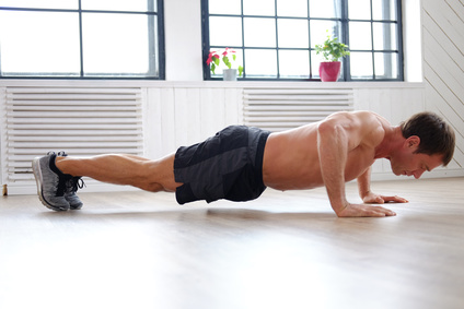 Oberkörpertraining ohne Geräte: Foto von einem Mann bei der Brust-Übung Liegestützen.