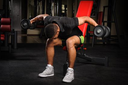 Obere Rückenmuskulatur trainieren: Foto von einem Mann bei der Rücken-Übung Seitheben vorgebeugt.