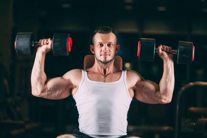 Schultermuskulatur aufbauen: Foto von einem Mann bei der Übung Schulterdrücken mit Kurzhanteln.