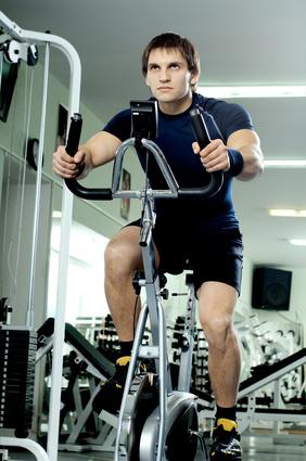 Unterschenkel trainieren: Foto von einem Mann beim Radfahren Intervalltraining auf dem Hometrainer.