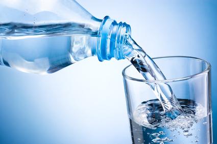 Bauchspeck weg Ernährung: Foto von einer Wasser Flasche und einem Glas.