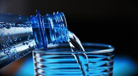 Fettverbrennungstipps: Foto von einer Flasche Wasser und einem Glas als optimale Wassermenge.