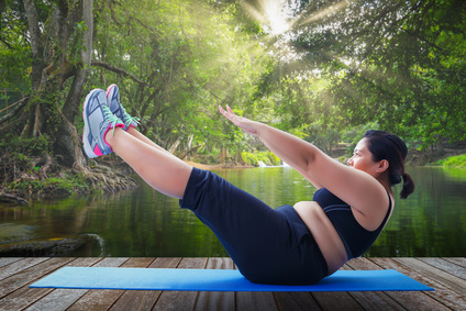 Tägliches Bauchmuskel-Training: Foto von einer dicken Frau beim Sixpack Training.