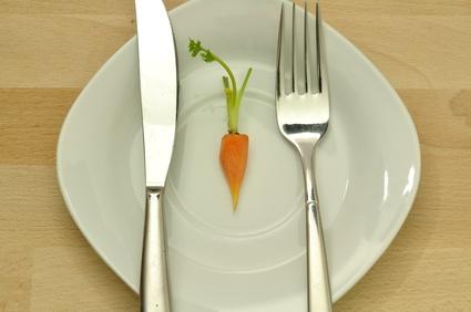 Wie realistisch ist ein Waschbrettbauch: Foto von einem Teller mit einer kleinen Karotte darauf als Hungern Symbol.