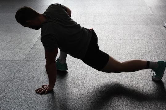 Foto von einem Mann beim Muskulatur dehnen auf dem Boden.