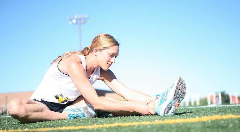 Foto von einer Frau beim Muskulatur dehnen auf dem Boden.