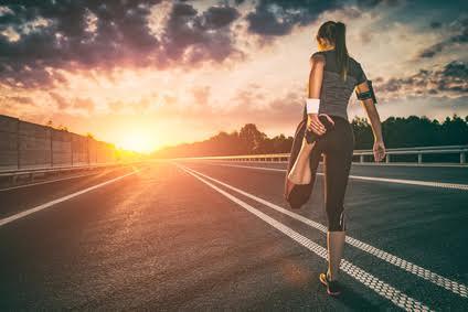 Foto von einer Frau beim Muskulatur dehnen mit Sonnenuntergang im Hintergrund.